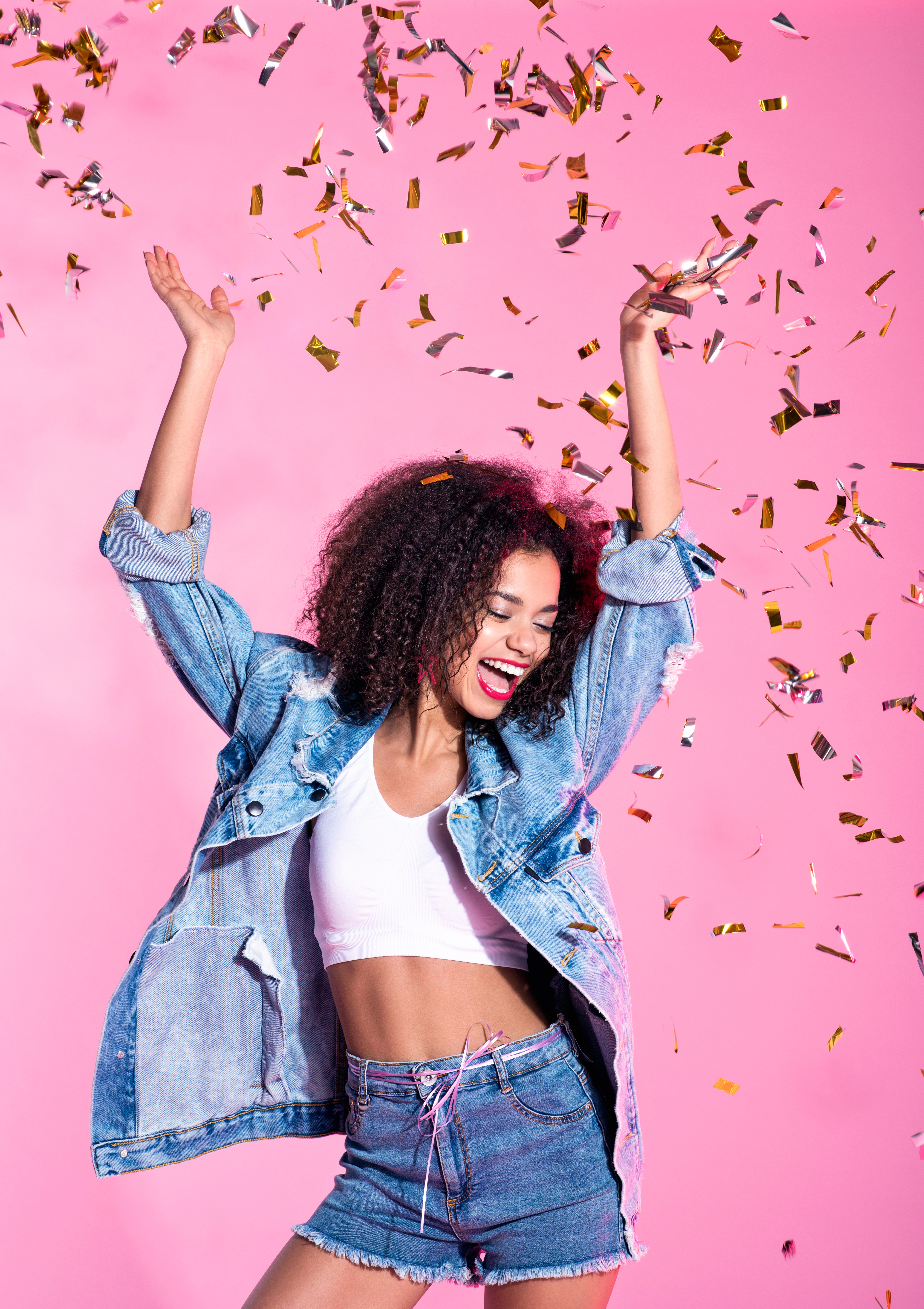 Portrait of happy young afro woman among confetti