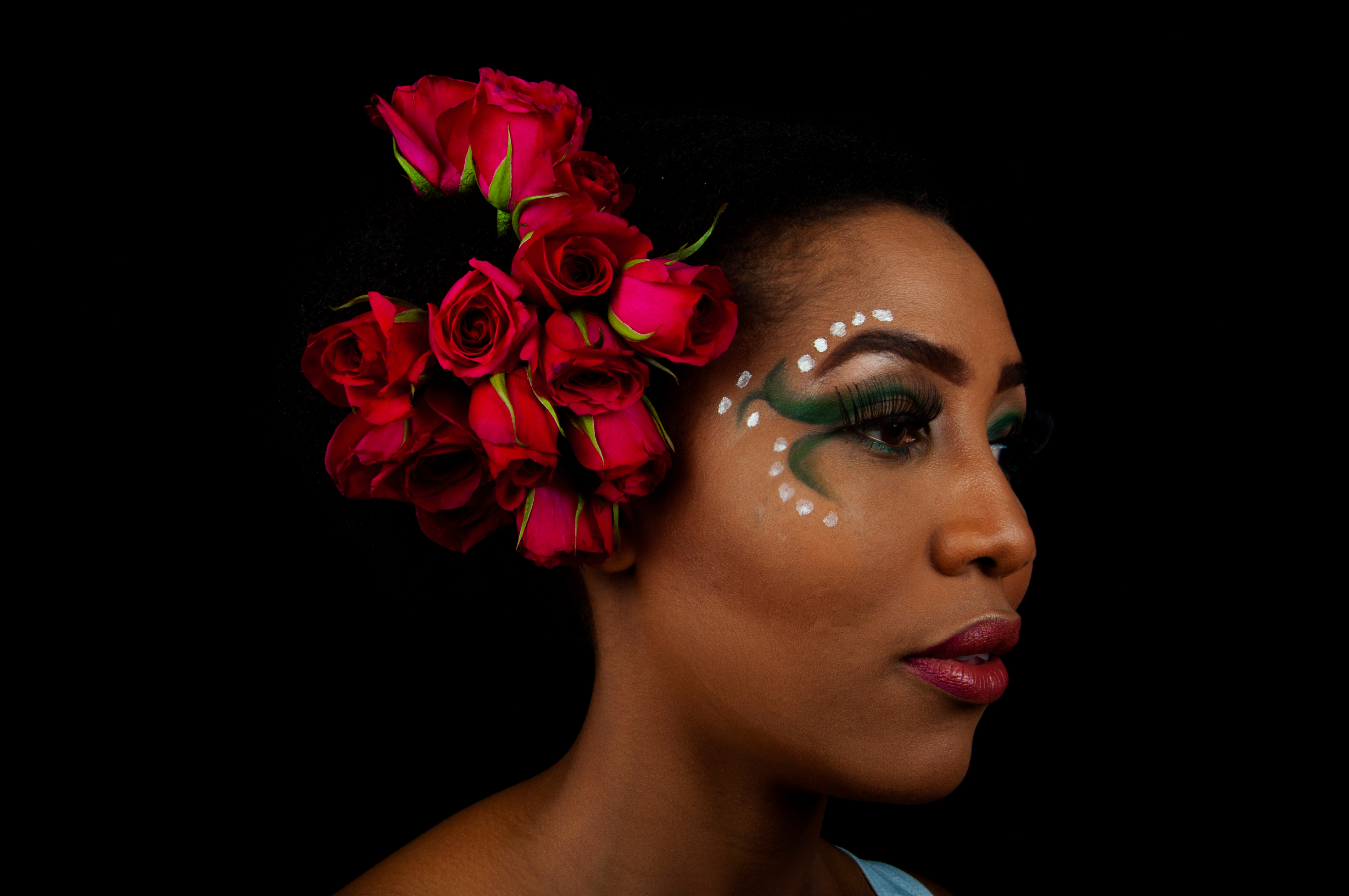 Close-Up Of Woman Wearing Roses With Face Paint Over Black Background