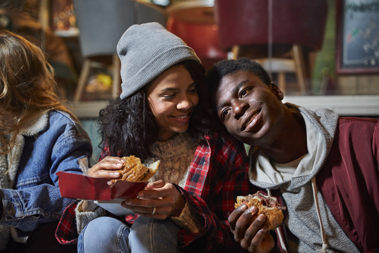 Man and woman resting while having burger in city