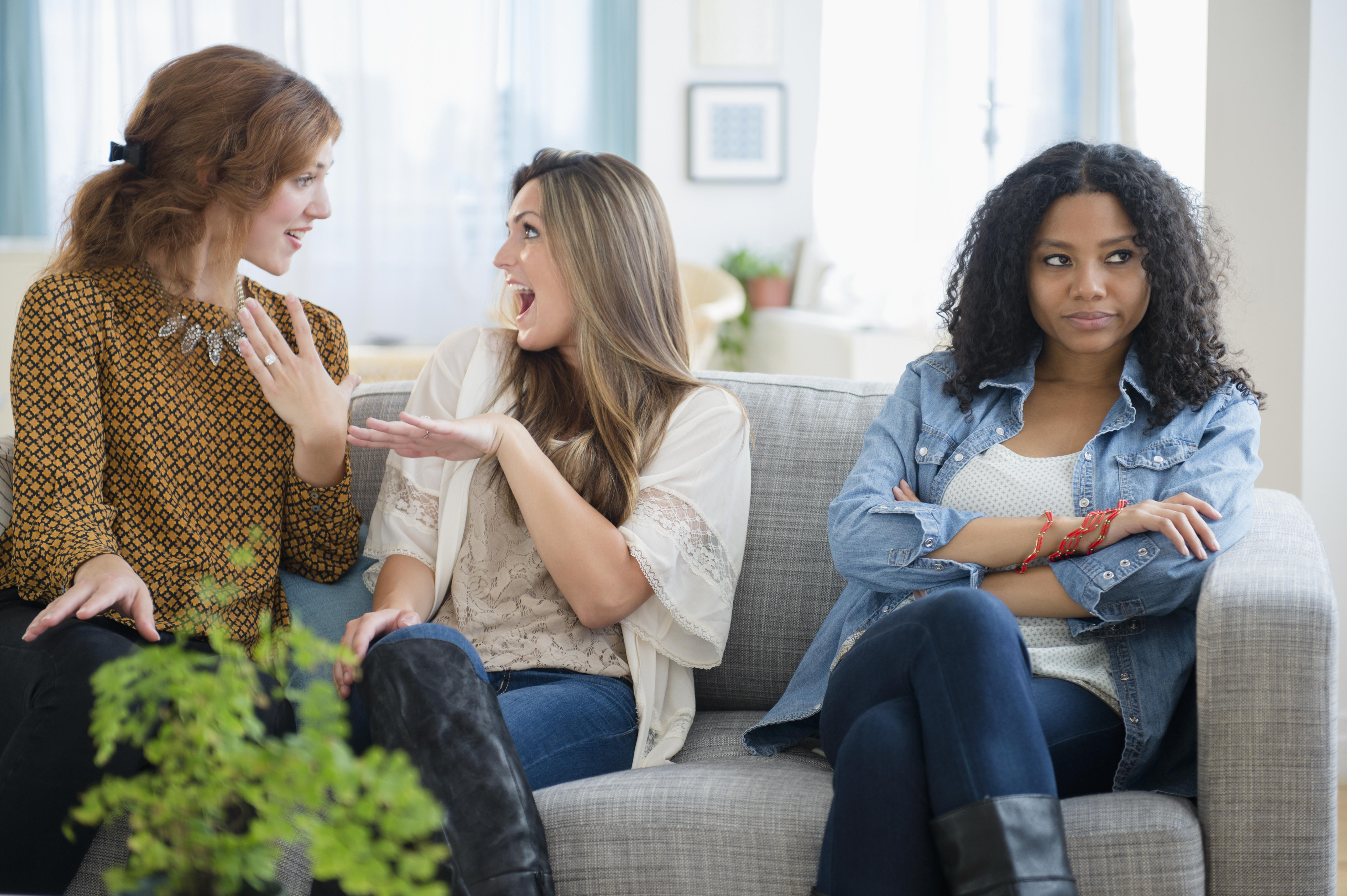 Chatting women ignoring upset friend on sofa