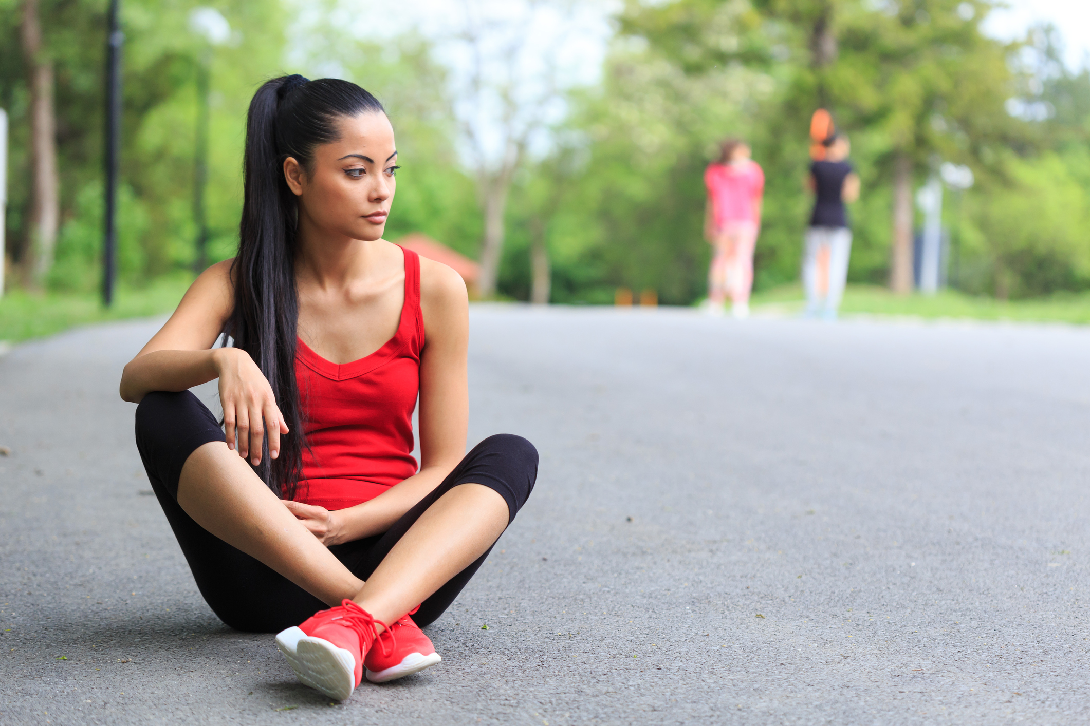 Young sportswoman resting on ground