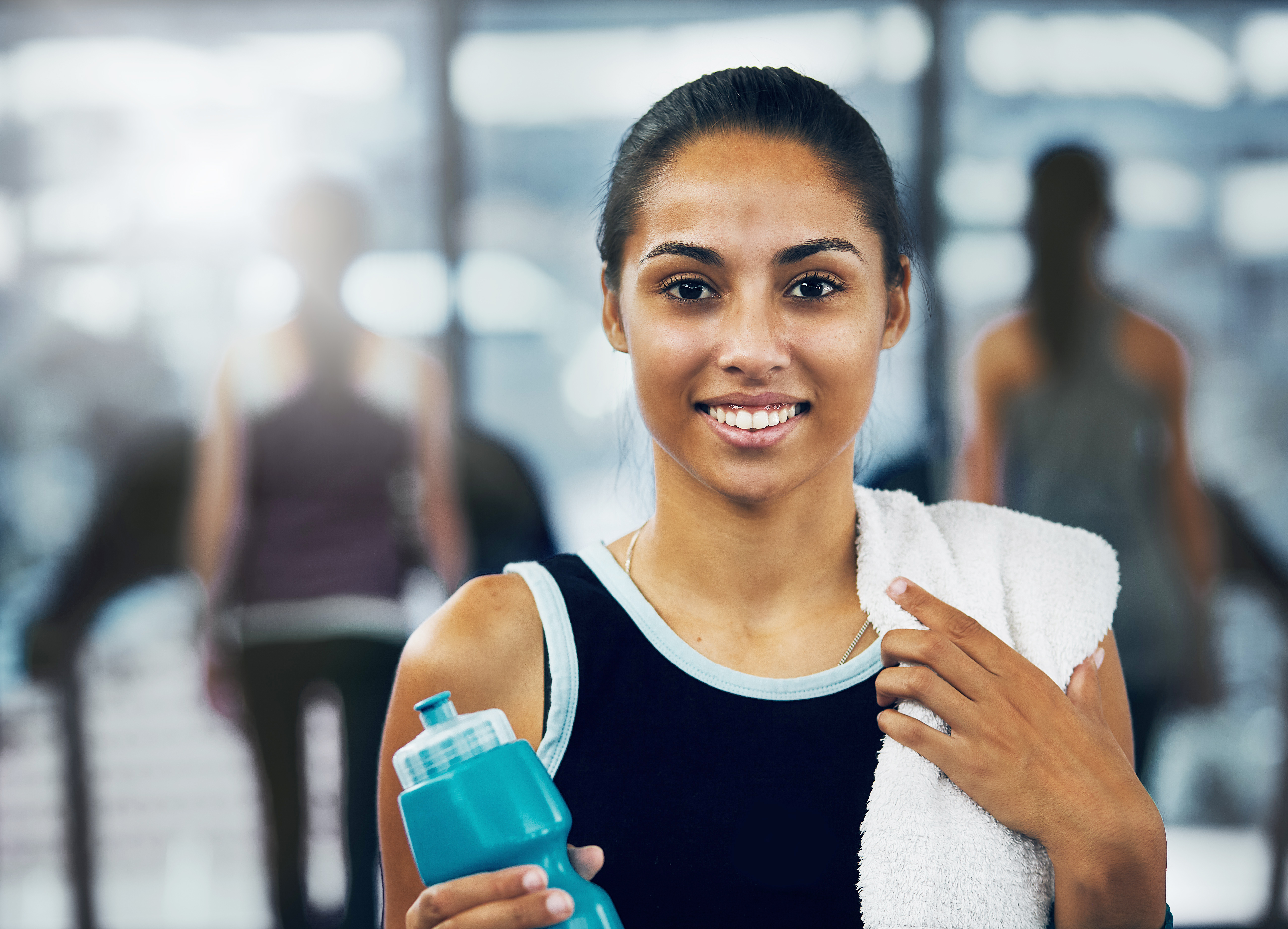Beautiful young woman smiling after exercising at gym