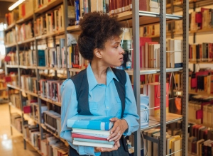 Young woman holding handful of books