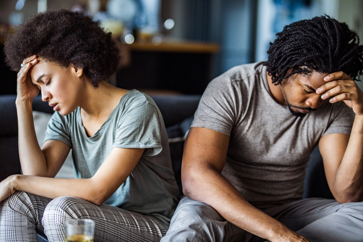Young black couple feeling sad after arguing on sofa at home.