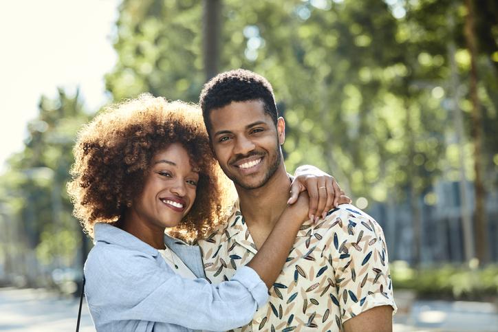 Smiling woman embracing man on sidewalk in city