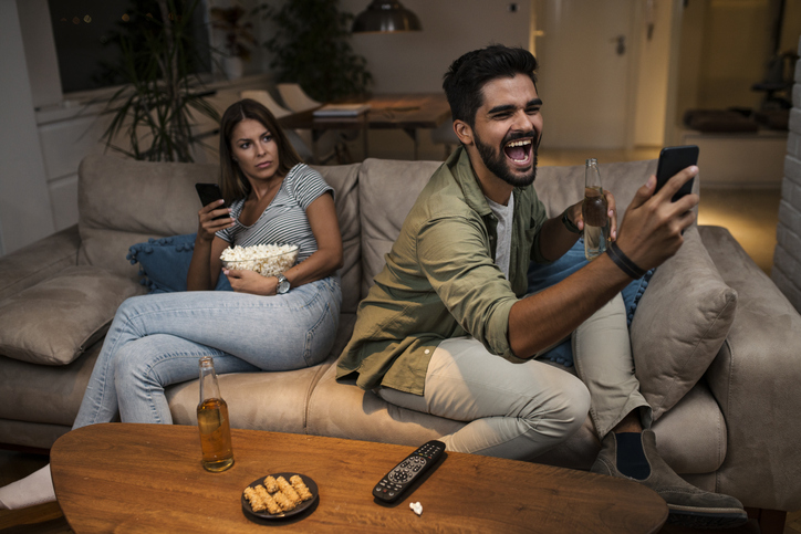 Young couple spend their evening at home using a smartphone