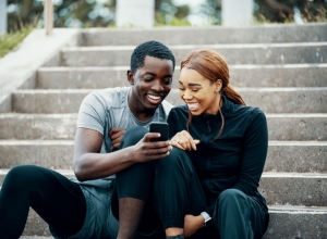 Young athletic couple looking at a smart phone before or after running or jogging