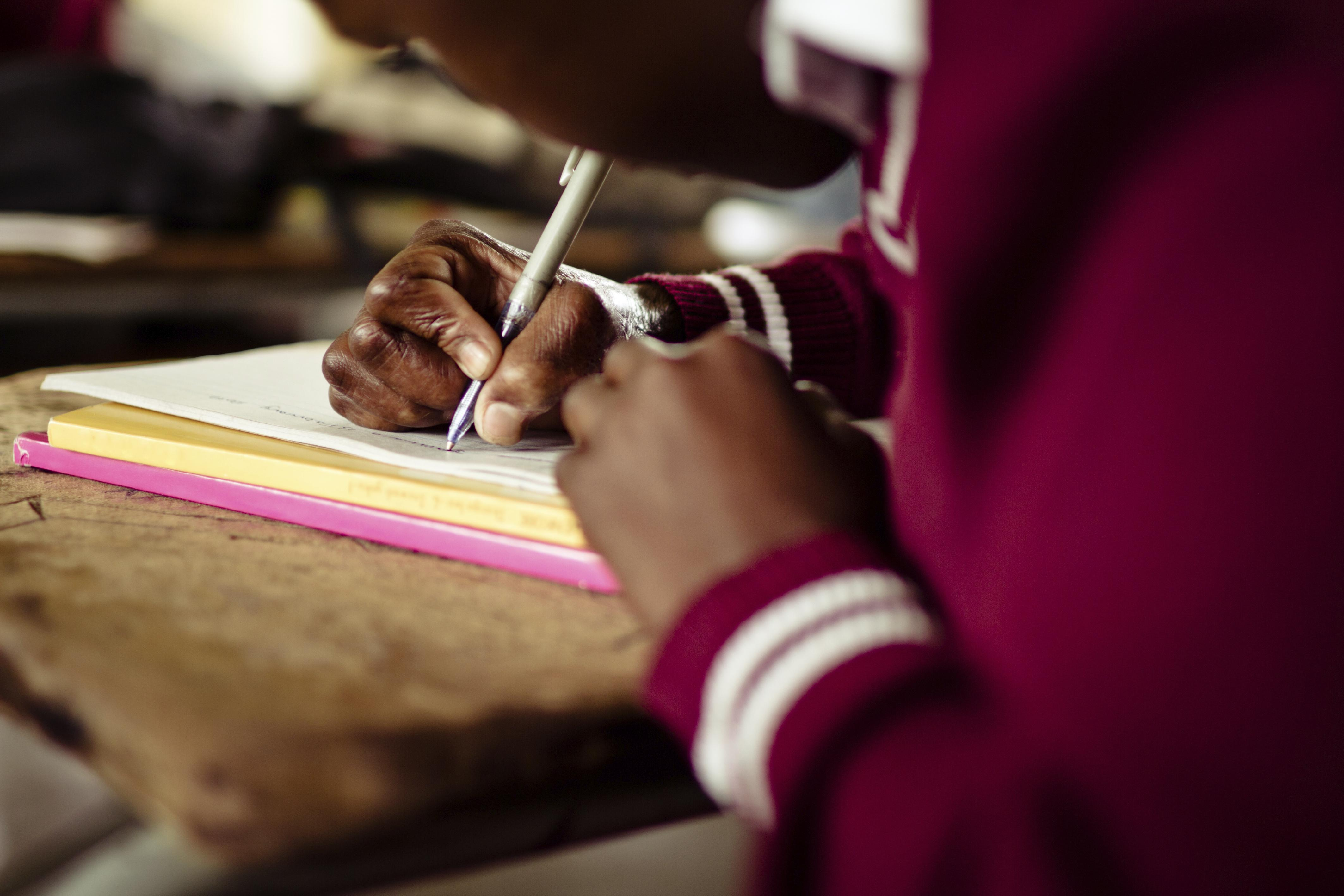 Closeup image of South African girl writing at her desk