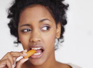Unhappy woman eating a carrot