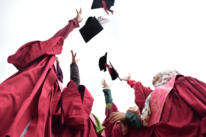 Low Angle View Of Students Throwing Mortarboard Against Sky
