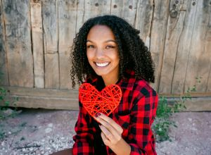 Portrait Of Smiling Young Woman Holding Heart Shape
