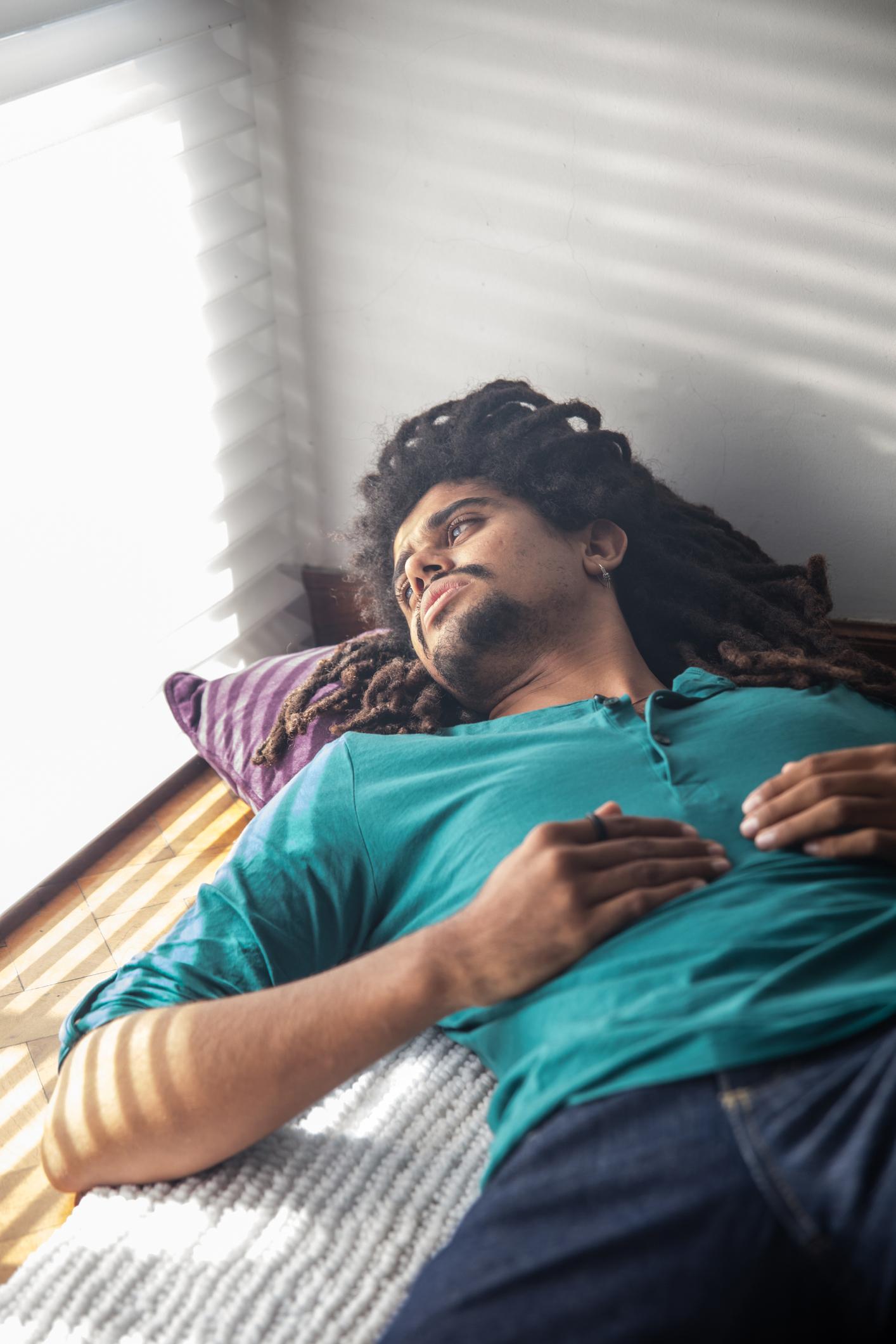 Thoughtful rastafarian lying down on floor at home looking away