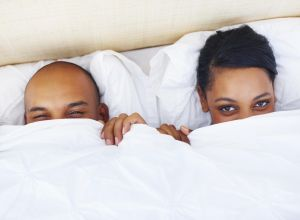 Young couple in bed doing peek-a-boo with you