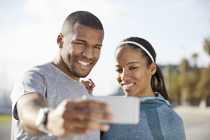 Smiling couple taking selfie at park on sunny day