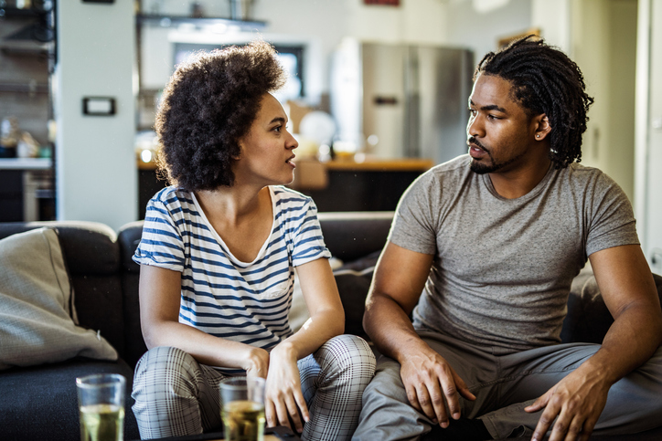 Young African American couple talking in the living room.