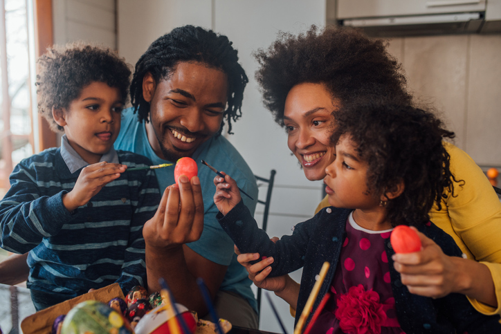 Family with children decorating Easter eggs