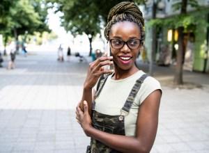 African woman talking on phone on street