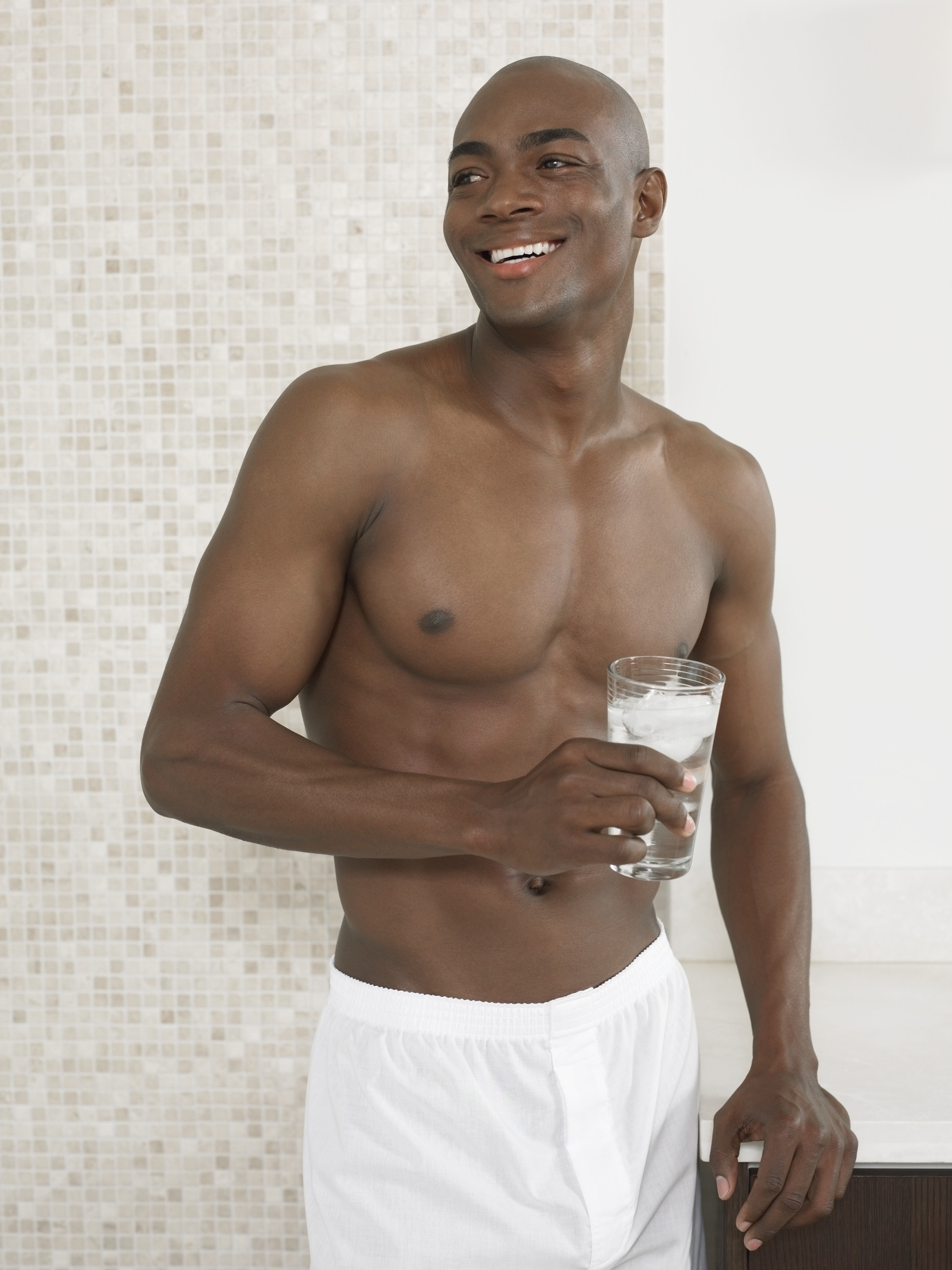 Man Stands in Bathroom in His Boxer Shorts Holding a Glass of Water