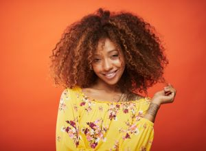 Beautiful afro Caribbean young woman in summer clothes against orange background.