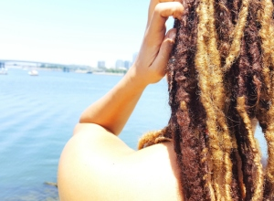 Rear View Of Woman With Dreadlocks Standing By Sea Against Clear Sky