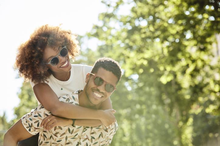 Young couple enjoying piggyback ride on sunny day