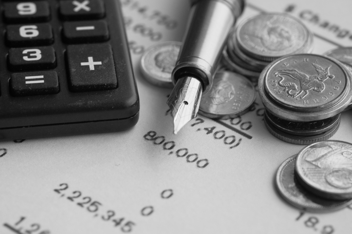 top view of coins, pen calculator and accounting document