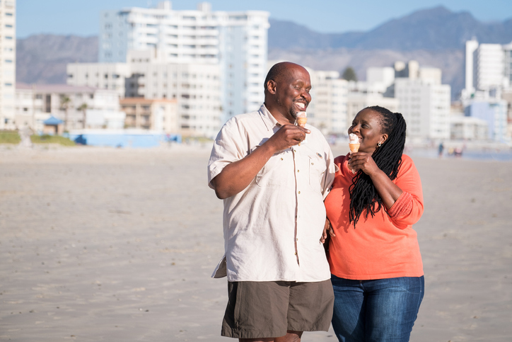 Loving mature couple eating ice creams at beach