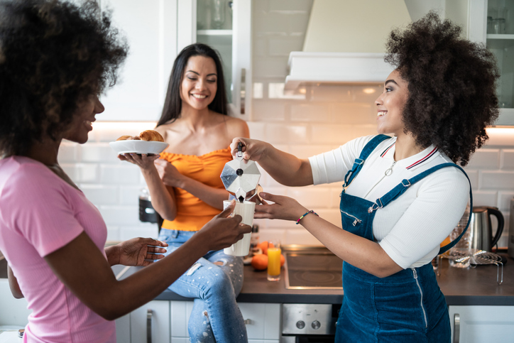 Happy Girlfriends having breakfast together at home