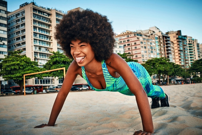 young woman doing push ups on the beach