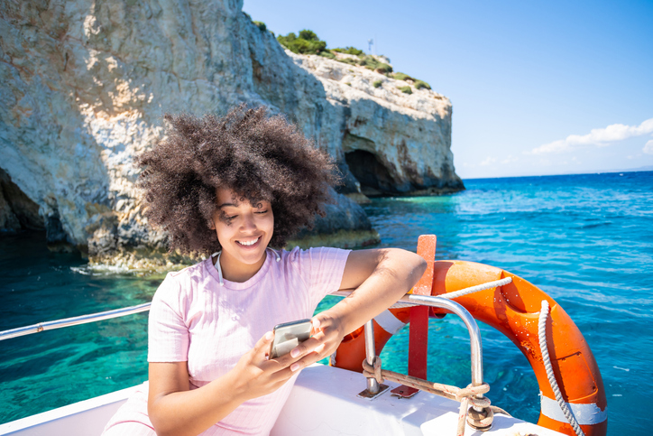 Afro woman sitting on yacht and using smart phone in Zakynthos Greece - Navagio beach