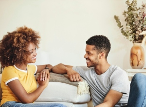 Cheerful couple looking at each other in room