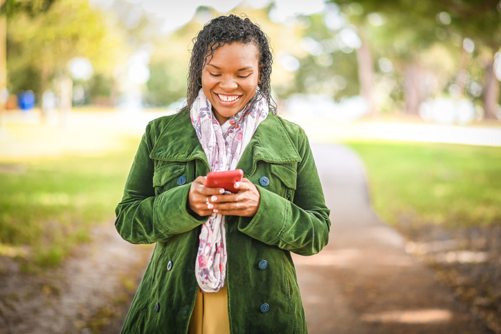 African American woman uses cell phone outdoors in a light jacket