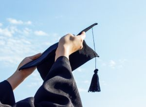 Low Angle View Of Hands Holding Mortarboard Against Sky During Sunny Day