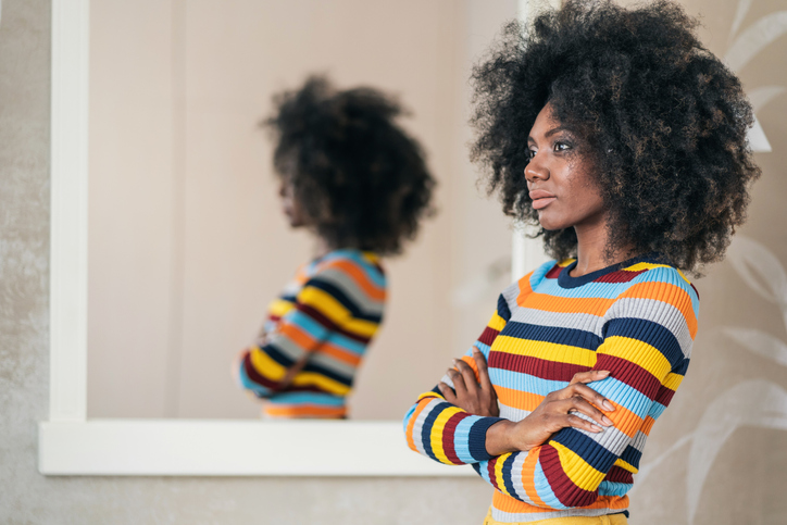 Afro Woman standing in front on the mirror
