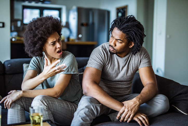 Angry African American couple arguing in the living room.