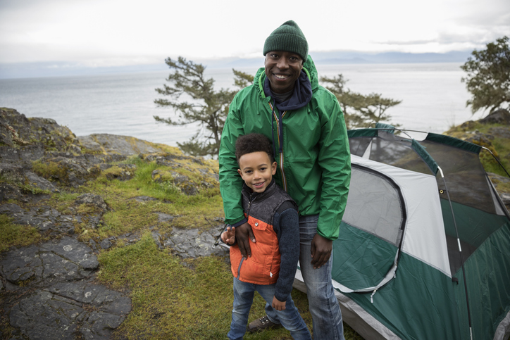 Portrait smiling father and son camping