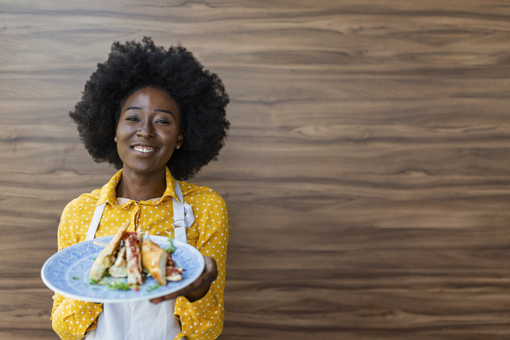 Waitress carrying a plate with sandwich