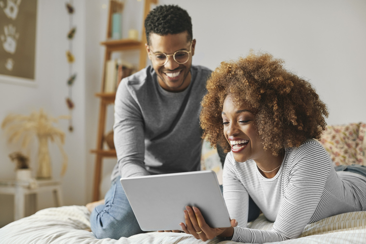 Cheerful couple sharing digital tablet at home