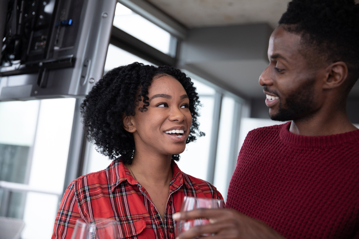Young and happy black couple celebrating inside their condominium with red wine.
