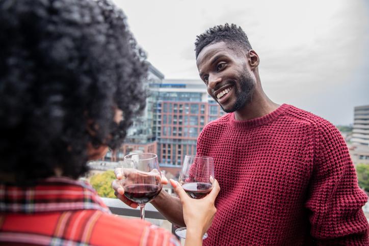 Happy black couple having red wine on the balcony of their new condominium in Toronto.