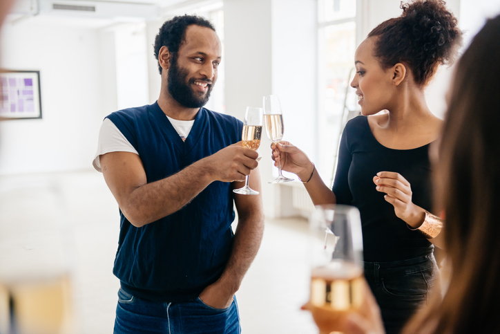 Two african visitors touching glasses during a gallery opening