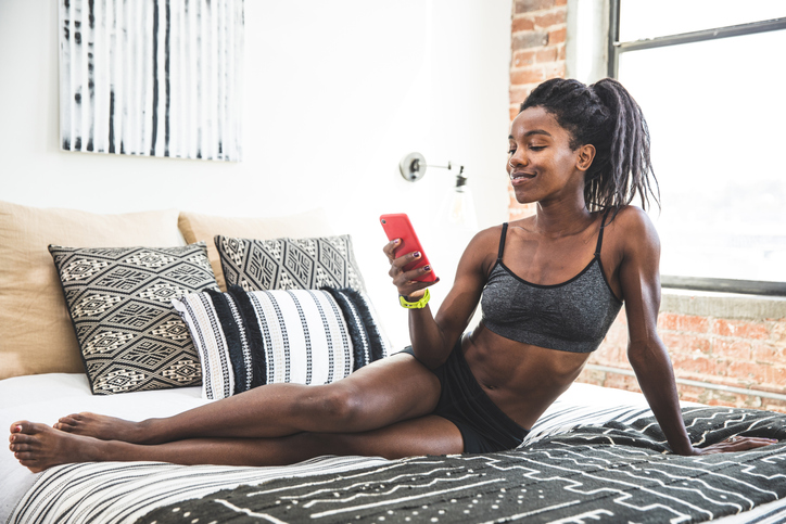 Afro american woman chilling out on the bed after work out
