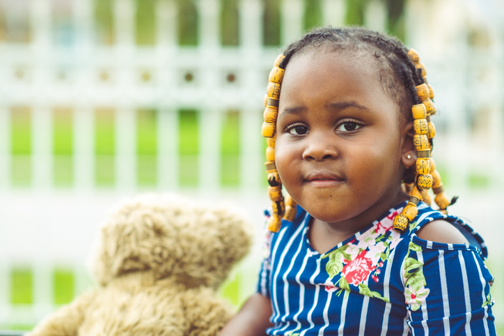 Outdoor portrait of an adorable chubby 3 year old toddler with beads and braids