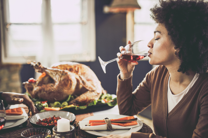 Profile view of black woman drinking wine on Thanksgiving lunch.