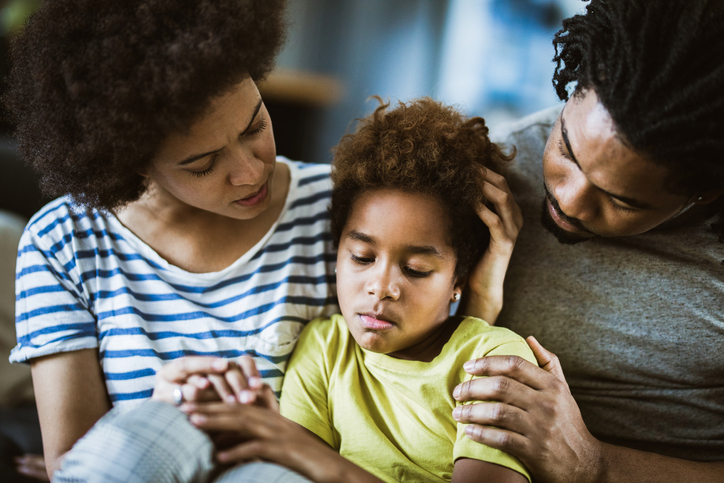 African American parents consoling their sad girl at home.
