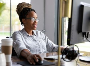 Mid adult female boss smiles as she works at computer