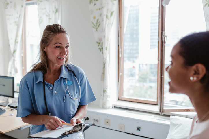 Smiling female nurse talking with patient in hospital
