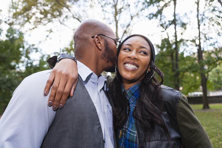 Man kissing womans cheek in park