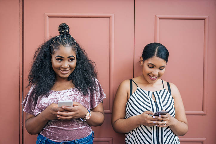 Two obese young women using phones
