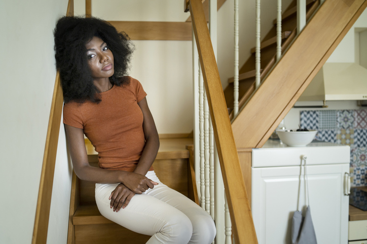 Sad african woman sitting on stairs at home